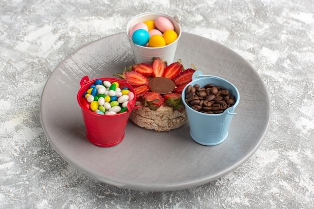 Biszkopt z truskawkami na fioletowym talerzu wraz z ziarnami kawy i cukierkami na szaro