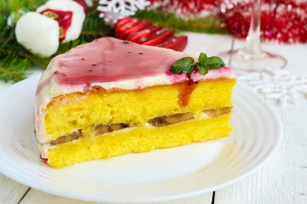 Biszkopt z warstwą banana, śmietanki i syropu żurawinowego. wakacyjny deser. motyw bożego narodzenia.