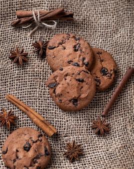 Biszkopty z czekoladą, laskami cynamonu i badianem leżą na tle materiału jgutowego. pieczywo. słodycze, jedzenie, przyprawy