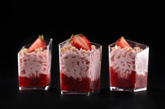 Bita śmietana z różową śmietaną i czerwonym dżemem ozdobione świeżymi truskawkami i białymi, chrupiącymi kulkami czekoladowymi na wierzchu. słodkie desery serwowane w trzech małych szklankach w rzędzie na białym na czarnym tle.