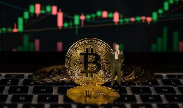 Bitcoin biznesmen zabawka i tło wykresu giełdy
