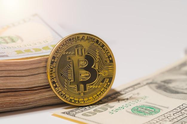 Bitcoin btc dołączony do monety kryptowaluty na stosie 100 setek nowych dolarów amerykańskich pieniądze american wirtualna technologia blockchain przyszłość to koncepcja pieniądza zbliżenie i fotografia makro światło słoneczne tło