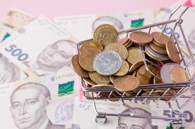 Bitcoin i monety w koszyku na tle banknotów hrywny