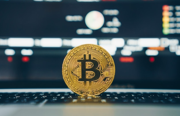 Bitcoin kryptowaluta cyfrowa replika monety złotej monety na laptopie z giełdą handlową finansową na ekranie. koncepcja finansowania firmy.