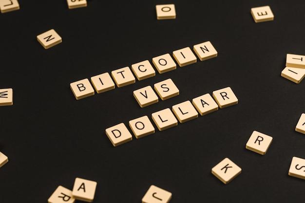 Bitcoin kryptowaluta kontra koncepcja, słowo dolara na czarnym tle, kreatywne zdjęcie pomysłu