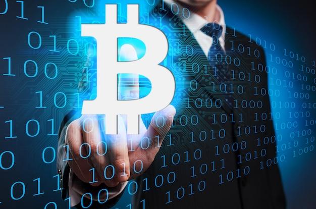 Bitcoin mężczyzna w garniturze i krawacie klika palec wskazujący na wirtualnym ekranie.