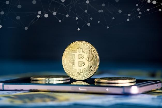 Bitcoin moneta na ekranie telefonu na tle banknotów euro.