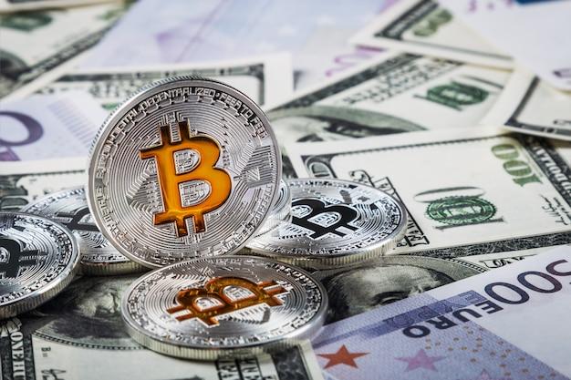 Bitcoin monety na tle banknotów dolarów i euro