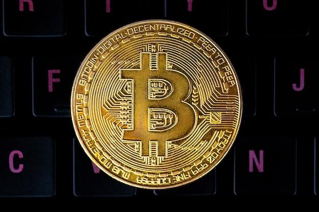 Bitcoin na klawiaturze komputera na powierzchni, symbol elektronicznych wirtualnych pieniędzy i koncepcja kryptowaluty wydobywczej