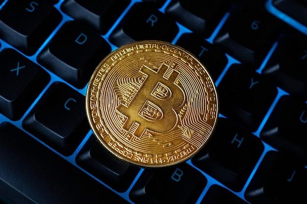 Bitcoin na klawiaturze komputera w tle, symbol elektronicznych wirtualnych pieniędzy i koncepcja kryptowaluty wydobywczej. bitcoin kryptowaluty monety leży na klawiaturze. bitcoin na klawiaturze.
