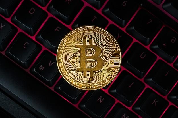 Bitcoin na klawiaturze komputera w tle, symbol elektronicznych wirtualnych pieniędzy i koncepcja kryptowaluty wydobywczej.