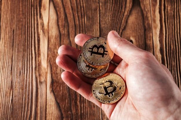 Bitcoin w rękach odizolowywać na drewnianym tle