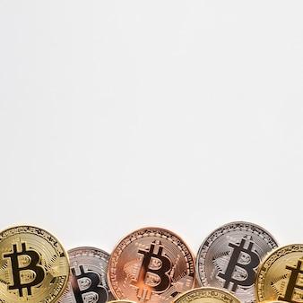 Bitcoin w różnych kolorach na prostym tle