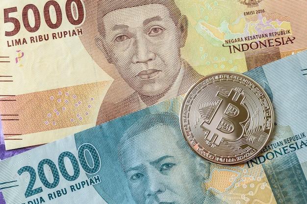 Bitcoin z aktualnymi banknotami rupii indonezyjskiej