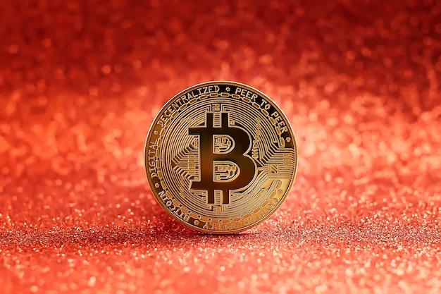 Bitcoin złota moneta i niewyraźne tło wykresu.