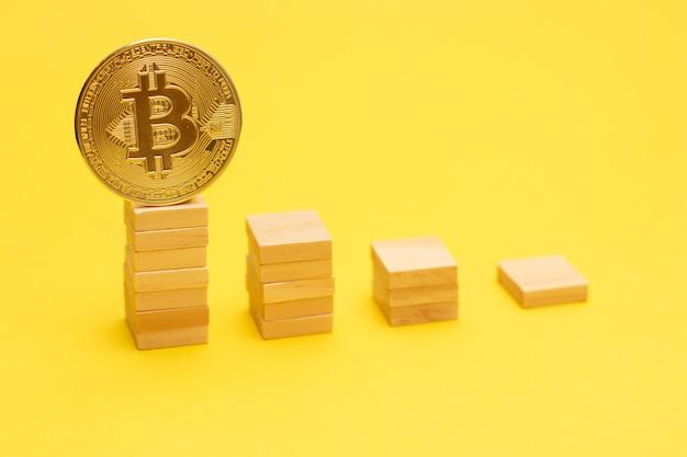 Bitcoin złota moneta na drabinie z drewnianych klocków.