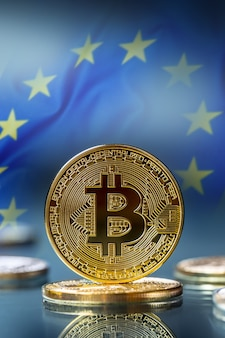 Bitcoin. złote i srebrne bitcoiny - wirtualna kryptowaluta. flaga unii europejskiej w tle