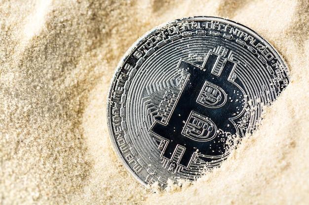 Bitcoinowa moneta tonie w piasku,