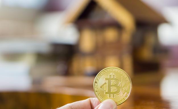 Bitcoinowa moneta w ręku. kupno i sprzedaż nieruchomości za pomocą bitcoin