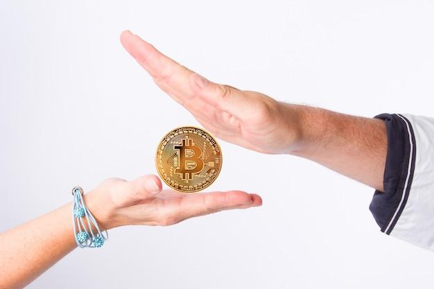 Bitcoiny, kryptowaluty, pieniądz elektroniczny w rękach mężczyzny i kobiety