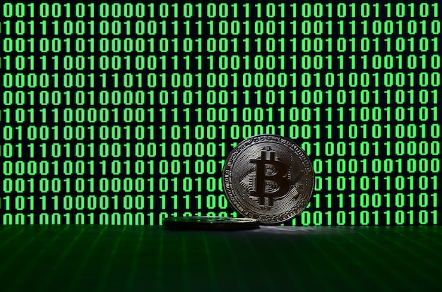 Bitcoiny znajdują się na tekturowej powierzchni na tle monitora przedstawiającego kod binarny