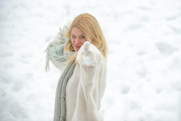 Bitwa na śnieżki. ludzie w śniegu. portret młodej kobiety w śniegu próbuje się ogrzać. radosny