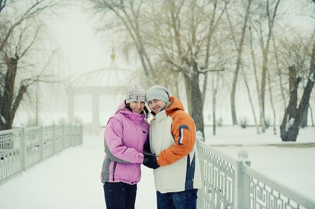 Bitwa na śnieżki. zimowa para zabawy grając w śniegu na świeżym powietrzu
