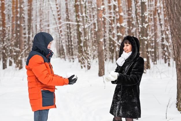 Bitwa na śnieżki. zimowa para zabawy grając w śniegu na zewnątrz.