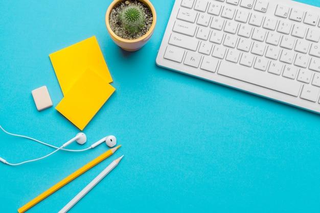 Biura stołowy biurko z dostawami na błękitnym tle, odgórnym widoku i kopii przestrzeni