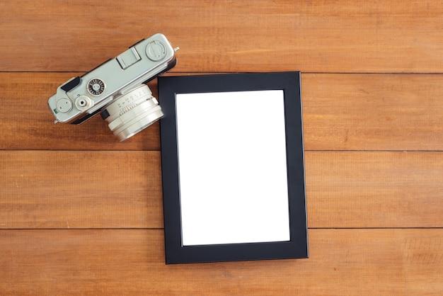 Biurka drewniany stół z stary aparat i plakat makieta szablon. widok z góry z miejsca na kopię