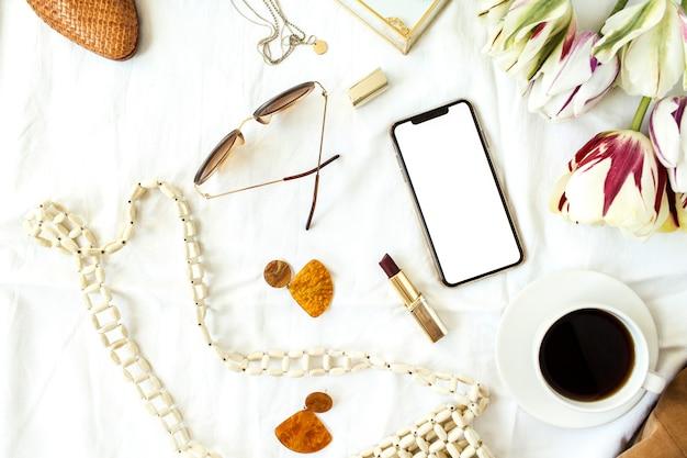 Biurko biurko biurkowe pusty ekran inteligentny telefon, bukiet kwiatów tulipanów, ubrania i akcesoria na białej pościeli