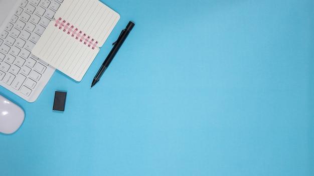 Biurko biurko z zestawem kolorowych materiałów eksploatacyjnych, niebieski notes pusty, kubek, długopis, komputer, zmięty papier, kwiat na niebieskim tle. widok z góry i kopiowanie miejsca na tekst.