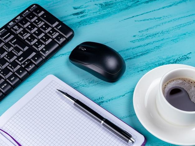 Biurko biurkowe. obszar roboczy z notatnikiem, klawiaturą, artykułami biurowymi i filiżanką kawy na drewnianym tle.