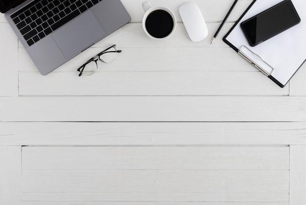 Biurko biurowe drewniane typu flat lay, top view. obszar roboczy z pustym schowkiem, laptopem, myszką, smartfonem, okularami, filiżanką kawy, artykułami biurowymi