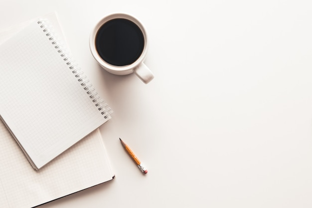 Biurko biurowe z zapasami, filiżanką kawy i kwiatkiem. widok z góry z miejscem na kopię