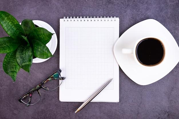 Biurko biznesowe z artykułami biurowymi, notatnikiem, długopisem, kwiatkiem, okularami na ciemno.