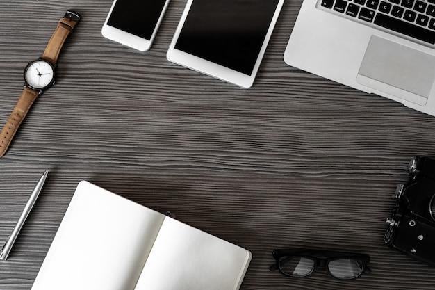 Biurko biznesowe z laptopem, telefonem, cyfrowym aparatem do tabletu, długopisem, okularami i zegarkiem na ciemnym drewnianym pustym stole nowoczesny blat do pracy z urządzeniami, obszar roboczy widok z góry z góry
