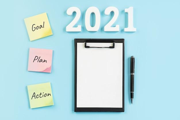 Biurko biznesowe z notatkami celu, planu i działań na rok 2021 na niebiesko, widok z góry z miejscem na kopię