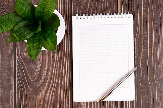 Biurko biznesowe z notesem, długopisem, kwiatkiem, okularami na drewnianym.