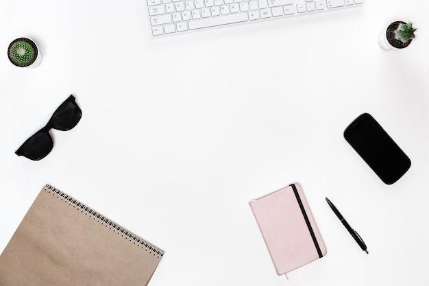 Biurko bloggera z białą klawiaturą, smatfonem, kaktusem i różowym pamiętnikiem