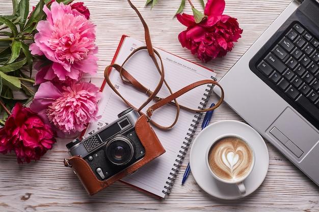 Biurko damskie leżące na płasko. żeński workspace z laptopem, różowym peonia bukietem, kamerą i kawą na białym tle.