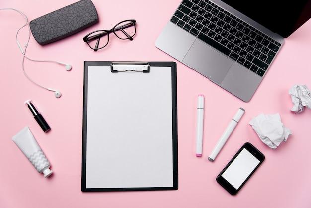 Biurko damskie różowe z czystą kartką papieru z bezpłatną przestrzenią do kopiowania, laptop, telefon z pustym białym ekranem, krem, szminka, słuchawki, okulary i materiały eksploatacyjne.