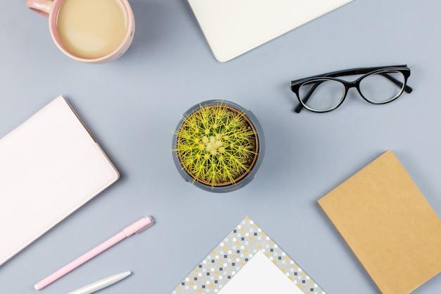 Biurko do biura domowego. kobiece miejsce do pracy z notatnikiem, okularami, kubkiem herbaty, pamiętnikiem, rośliną. skopiuj miejsce