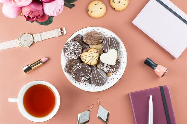 Biurko do biura domowego. kobiecy obszar roboczy z pamiętnikiem, kwiatami, słodyczami, modnymi akcesoriami. koncepcja blogera mody.