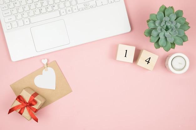 Biurko do biura domowego. kobiety miejsce do pracy z laptopem, kosmetykami, perfumami, akcesoriami na różowej powierzchni. koperta list miłosny, walentynki czerwone serce