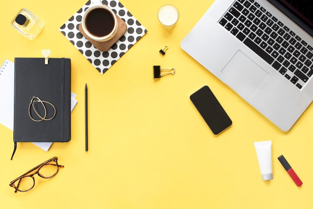 Biurko do domowego biura. kobiece miejsce do pracy z laptopem, telefonem, ołówkiem, świecą, akcesoriami kosmetycznymi dla kobiet, kubkiem kawy, czarnym pamiętnikiem na żółtym tle. widok płaski, widok z góry. wygląd bloga modowego.