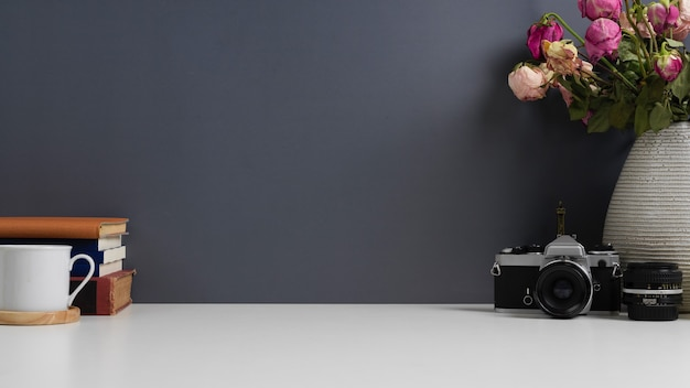 Biurko domowe z aparatem, książkami, filiżanką, miejscem na kopię i wazonem ozdobionym na stole