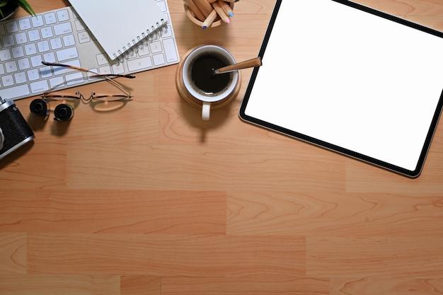 Biurko drewniane biurko z pustego ekranu tabletu, aparat fotograficzny, filmy i materiały biurowe