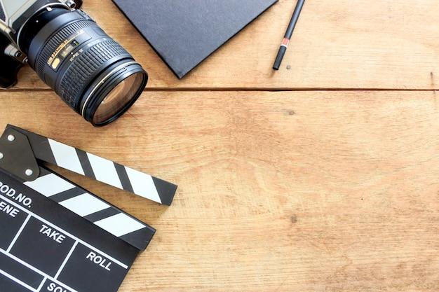 Biurko dyrektora filmowego. clapboard, książka i aparat cyfrowy na stole drewna