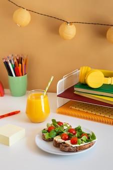 Biurko dziecięce z wysokim kątem z kanapkami i sokiem pomarańczowym